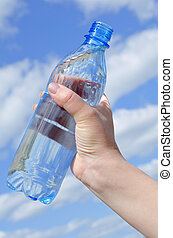Water bottle in a hand against the sky