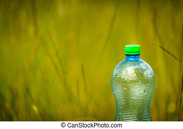 Water bottle on green grass with copy space.