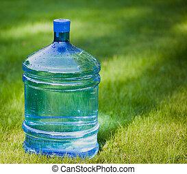 water bottle on green lawn background