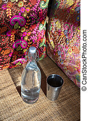 Water bottle on wood table with colorful pillow background in indian cafe