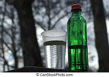Water bottle with glass on a background of blurred trees