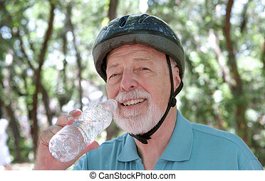 Water Break - A senior man taking a water break after riding...