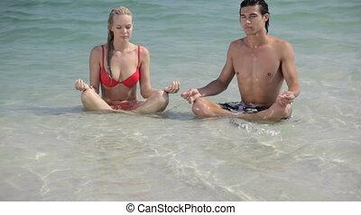 Water brings calmness - Guy and girl sitting in lotus pose...