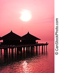 Water bungalows and sunset - abstract vacation background