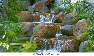 Water Cascades down a Multilevel Garden Waterfall - Video...