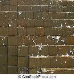 Water falling down on brown bricks