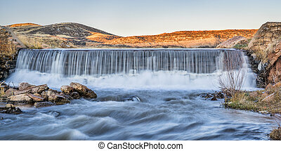 water cascading over a diversion dam in Colorado foothills