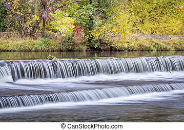 Water cascading over a diversion dam on the Poudre River with fall colors in bakcground