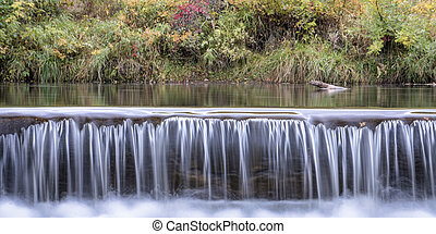 Water cascading over a diversion dam on the Poudre River with fall colors in background, panorama