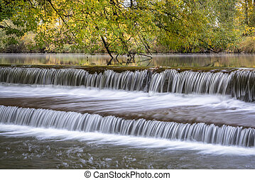 Water cascading over a diversion dam on the Poudre River with fall colors in background, nature and industry concept