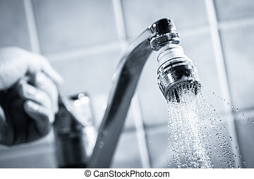 Water consumption - Open faucet and hand, water is running,...