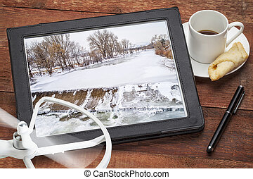 water diversion aerial photography concept - reviewing pictures of of a dam and river on a tablet with a drone and coffee, screen image copyright by the photographer