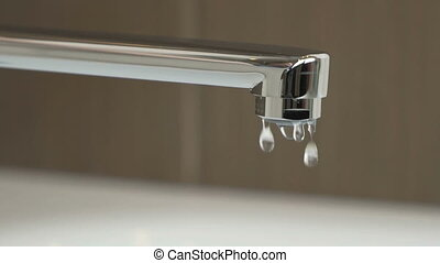 Water dripping from chrome-plated faucet