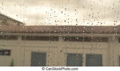 Water droplets on train window. Blurred sky and building....