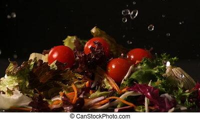 Water dropping onto fresh salad