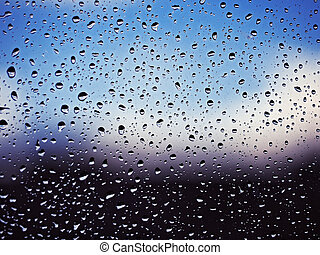 Water drops at the window glass at the blue sky with white clouds background