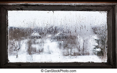 water drops from melting snow on frozen window