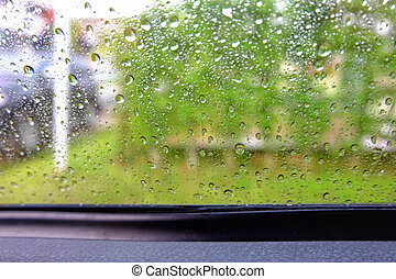 Water drops on car glass in a rainy day.