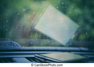 Water drops on car windshield with smartphone