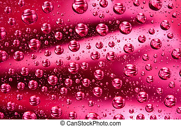 Water drops on red glass surface