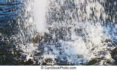 Water drops splashing on water surface in slow motion. Close...