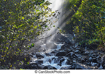 Water dust above the mountain river at day time.