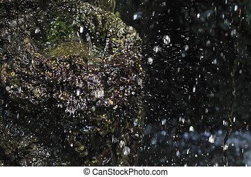 water fall on dark stone wall