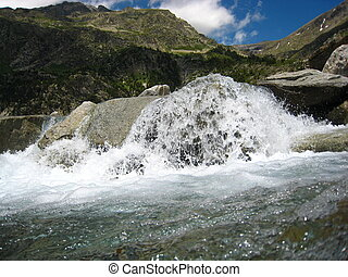 Water falling and flowing from rocks in a river mountain
