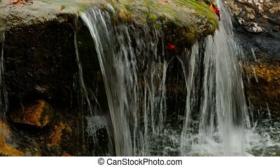 Water Falling In Small pond From Boulder Covered With Moss -...