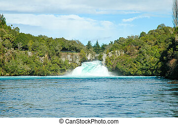 Water falls against a green forest and blue skies
