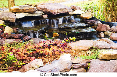 Water feature with rocks, ornamental plants, and flowing waterfall.