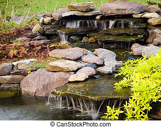 Water feature with rocks, ornamental plants, and flowing waterfalls.