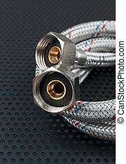 Water flexible hose in metallic braiding on a dark background