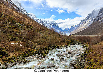 Water flow down from river to lake with snow cap mountain background
