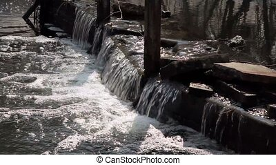 Water flow over big stones on dam in river, closeup view