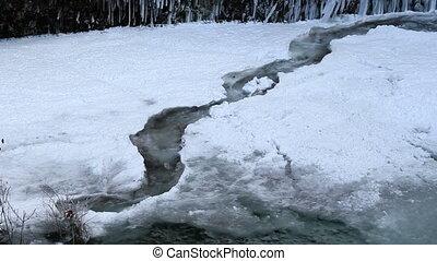 Water Flowing along Frozen Creek in Deep Freeze Winter...