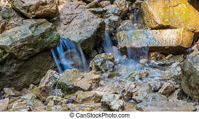 Water flowing among rocks in the summertime