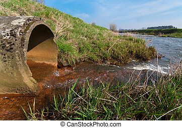 drain pipe - water flowing from a drain pipe into a small ...