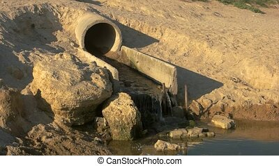 Water flowing from sewage pipe. Concrete and sand. Common...