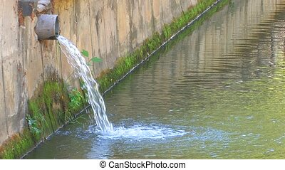Water flowing from the pipe into town river, Canon XH A1,...