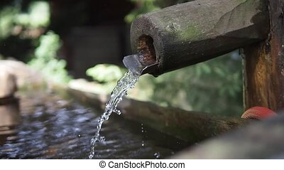 Water flowing from wooden pipe, fountain, waterplace