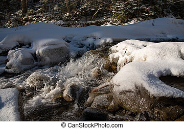 Water flowing in rapids over stone, in the winter mountains