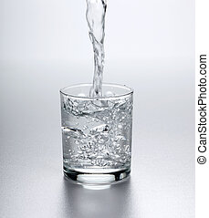 Water flowing into full glass