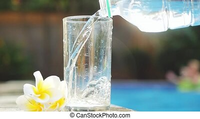 Water flowing into the glass next to swimming pool and frangipani flower in slow motion. Healthy lifestyle. 1920x1080