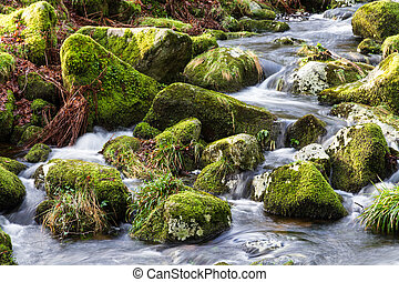 Water flowing over stones. near base of waterfall winter.