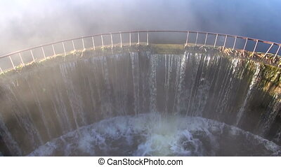 Water flowing through dam with fog rising in the morning