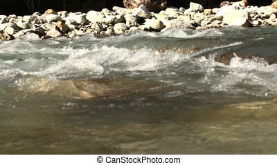 Water flowing - water flowing past rocks in a river bed