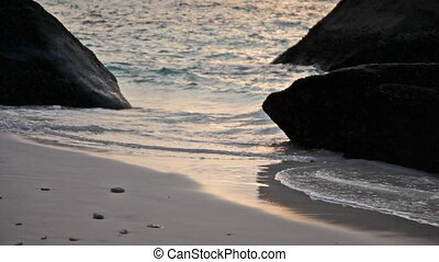water flows between two rocks in the sea at sunset