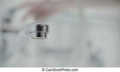 water flows from the tap close up slow motion