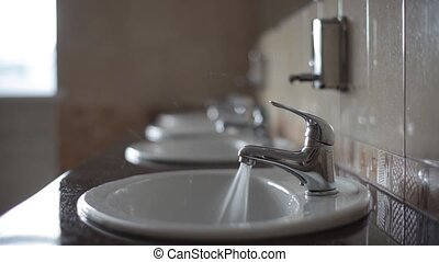 Water flows from the tap in a public toilet. Nobody here....